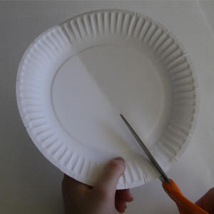 Fold and cut the paper plate in half.